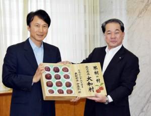 大和村特産のスモモを三反園知事(左)に贈る伊集院村長=9日、鹿児島市の県庁