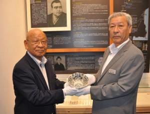 西郷隆盛からの贈り物を寄贈する久保さん(左)とその焼き物=2日、龍郷町