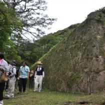 豪農が建てた巨大な石垣を見物する参加者ら=11日、龍郷町秋名