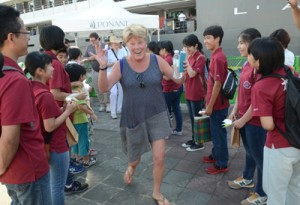 生徒から折り紙を贈られて笑顔を見せる乗客=4日、奄美市名瀬