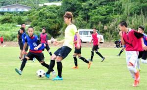 沖永良部島の子どもたちと一緒にサッカーをする日本代表の大迫勇也選手=24日、和泊町
