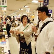 奄美黒糖焼酎の飲み方、魅力を説明する川崎景子さん(手前左)=8日、千葉県船橋市