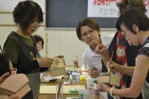 津田さん(右)の指導のもと、トールペイントを体験する参加者