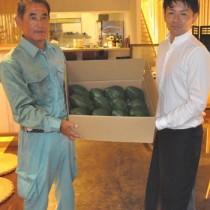 奄美パパイアのPRに向けて、果実を提供する熊元部会長(左)=19日、徳之島町亀津