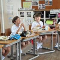 給食を食べ笑顔をみせる(左から2、3人目)イライジャ・和真君とバリシ君=19日、伊仙町面縄小学校