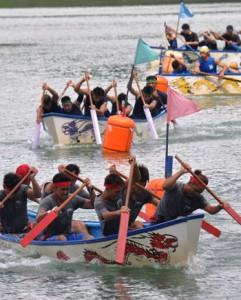 男子決勝で力強いかいさばきを見せる舟こぎの選手たち=23日、龍郷町