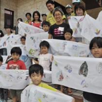 自分で作った葉っぱプリント手ぬぐいを広げる子どもたち=31日、大和村の奄美野生生物保護センター