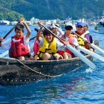 伴走船に見守られながら板付け舟での海峡横断に挑戦した生徒たち=30日、瀬戸内町