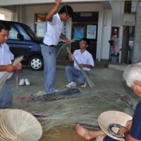 全国大会の舞台で使用する笠を作る沖高エイサー部の男子部員ら=14日、知名町