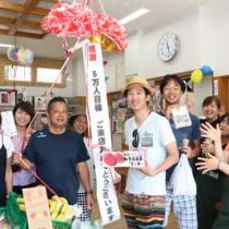 5万人目の来場者となった藤井誠さん(中央)と祝福する関係者ら=12日、瀬戸内町瀬相(提供写真)