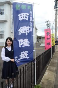 西郷ののぼり旗を揮ごうした大司さくらさん=8日、龍郷町