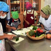 講師(右)のアドバイスに耳を傾けながら、材料の島野菜を調理する参加者=22日、奄美市笠利町