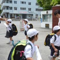 笑顔であいさつして下校する児童=20日、奄美市の名瀬小学校