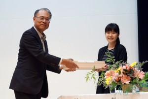 元田村長(左)から記念品の大島紬を受け取る福原さん=3日、宇検村元気の出る館(宇検村提供)