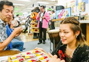ステージの合間に試食を手伝う澤愛香さん(右)。徳之島の商品をPRする高岡町長(中央)=3日、三越本店