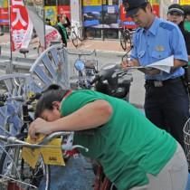 放置自転車にステッカーを取り付ける参加者=20日、奄美市