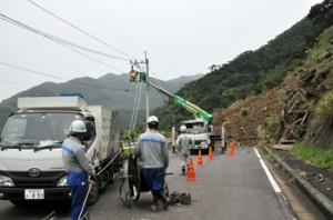 写真ヨコ 奄美市の市道・山間―戸玉間の土砂崩れ現場で行われた高圧配電線などの復旧作業=7日午前11時半ごろ、同市住用町