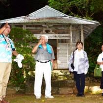 参加者に境内からの眺望の魅力を説明する東川さん(左)=21日、宇検村宇検の高千穂神社