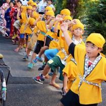 恒例の「子ども種おろし」。地区内を歌い踊り歩く子どもたち=19日、龍郷町中戸口