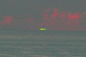 水平線に沈む夕日が鮮やかな緑色に包まれたグリーンフラッシュ(吉行秀和さん撮影)