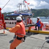 漂流者救助の患者引き継ぎ訓練を行う警察と消防署員ら=27日、奄美市名瀬観光船バース