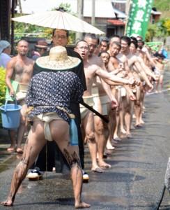 勇壮な掛け声を挙げながら集落内を練り歩く男衆=12日、宇検村芦検集落