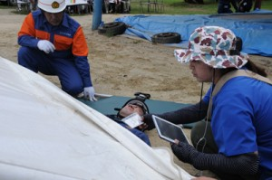 防災訓練で、タブレット端末を利用して患者の症状を医師に伝える請島の請畑看護師(右)=27日、瀬戸内町請島