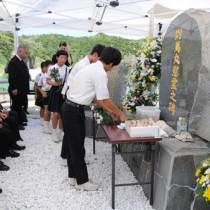 献花する久志小中の児童生徒=26日、宇検村の船越海岸