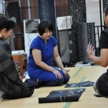 反物が並び関係者のアドバイスもあった展示販売会=26日、奄美市名瀬の紬会館