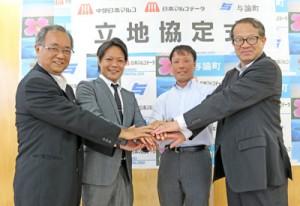 (左から)立地協定を結び握手を交わす山町長と、町田取締役、小板橋社長、五田部長=24日、与論町