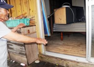 床上浸水の状況を説明する家主の男性=6日午前9時ごろ、瀬戸内町蘇刈