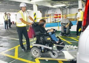 デモンストレーションで車いすのまま福祉車両に乗り込む利用者=1日、鹿児島市の鹿児島新港