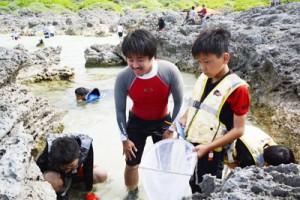 潮だまりの生物調査など、自然に親しみながらサンゴ礁を学ぶ参加者=1日、喜界町