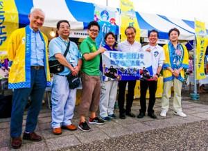 椎名山武市長(右から3人目)が奄美市のブースに来場し、交流拡大に期待した=7月29日、千葉県山武市