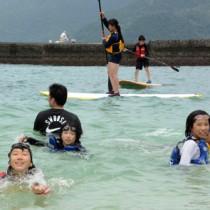 海遊びで交流する七ケ宿町と宇検村の児童=9日、宇検村タエン浜