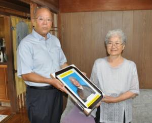 米寿の記念写真を受け取る原田カツエさん(右)=8日、奄美市笠利町