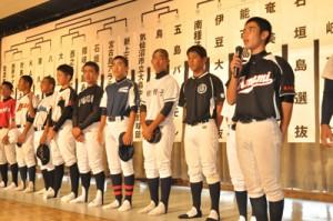 トーナメント表の前で、マイクを手にチーム目標を発表する奄美市選抜の渡主将(右)=21日、石垣市総合体育館