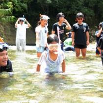 講師の興さん(左)とともに川の生き物を探す児童たち=19日、宇検村の河内川