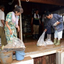 床上浸水で泥水に漬かった家屋内の片付け作業に追われる住民ら=5日午後2時45分ごろ、喜界町小野津