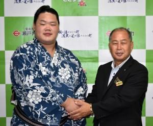 鎌田町長(右)と握手をする明生関=26日、瀬戸内町