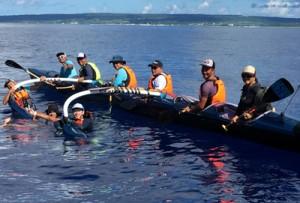 6人乗りカヌーで奄美大島―喜界島往復横断を達成した参加者。背景は喜界島(提供写真)