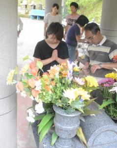 送り盆。精霊殿で祖霊に手を合わせる人々=5日、宇検村田検集落の共同納骨堂