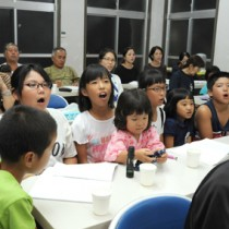 懸命に歌の練習をする子どもたち(上)と踊りの手本を見せる高齢者=22日、奄美市住用町の川内生活館