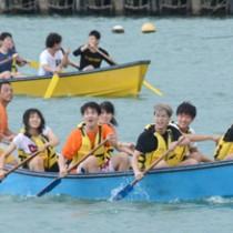 舟こぎ体験をする日本工学院八王子専門学校の学生=15日、奄美市名瀬小湊