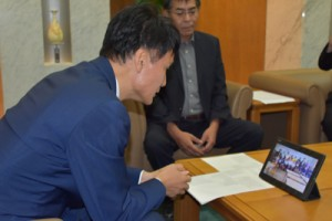 喜界島「さとうきびの会」からのビデオレターに見入る三反園知事(左)=21日、県庁の知事応接室