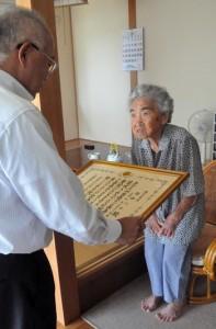 100歳の長寿を祝う賞状を受け取る作田ハルさん=16日、伊仙町喜念