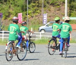 ヘルメットを着け、自転車に乗る児童たち=9月29日、龍郷町