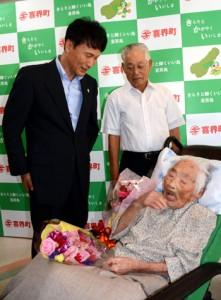 長寿世界一に認定される見通しの田島ナビさん(右)を訪問し、長寿を祝福する三反園訓知事(左)=18日、喜界町