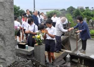 恒久平和を誓い、犠牲者の冥福を祈る参加者=25日、徳之島町亀津