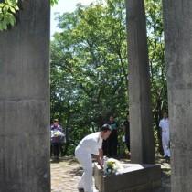 献花して犠牲者の冥福を祈る参列者=10日、奄美市